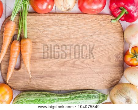 Wooden empty chopping board and vegetables near it.