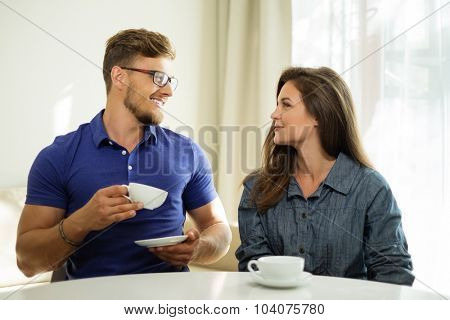 Cheerful couple behind table at home