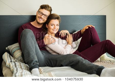 Cheerful couple on a bed at home