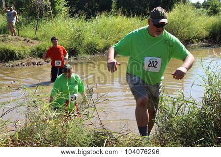 MUSKOGEE, OK - Sept. 12: Athlete try to avoid bloody zombies by going through muddy pond during the Castle Zombie Run at the Castle of Muskogee in Muskogee, OK on September 12, 2015.