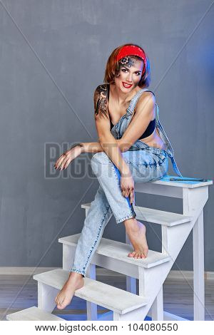 Girl Mechanic With Face Art Sitting On A Stepladder.