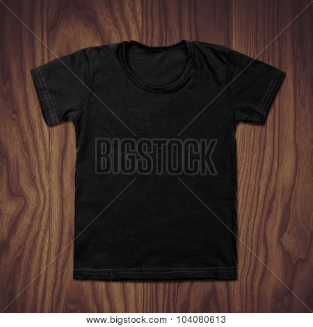 Black blank t-shirt on wooden background.