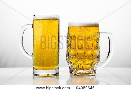 Two Mugs of fresh beer with cap  foam.