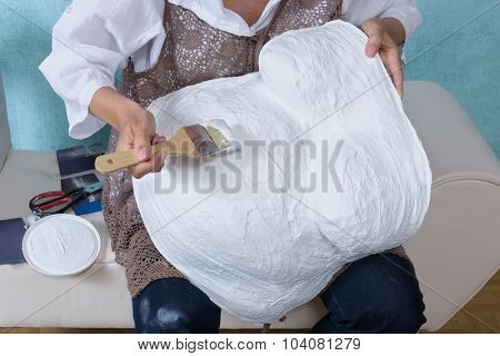 Woman painting a pregnancy belly cast with white primer, to enable decorating
