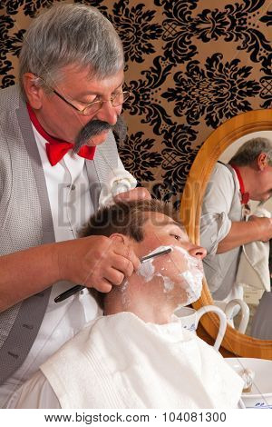 Antique barber shaving a customer with shaving cream