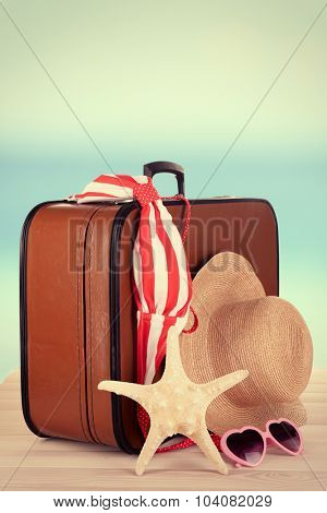 Suitcase and accessories for travelling on beach background