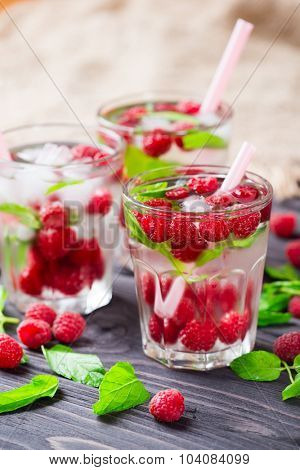 Cocktail with raspberry and mint in glass on a rustic wooden background