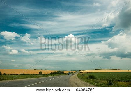 landscape owith road among fields at countryside