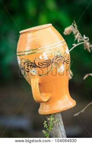 Ukrainian clay jug on wooden fence