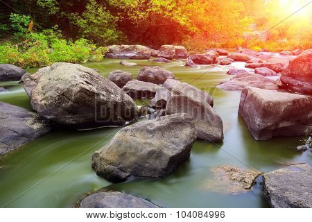 Evening scene on mountain river against sunset background