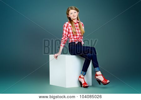 Full length portrait of a cute smiling teen girl posing at studio. Youth fashion.
