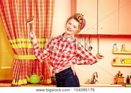 Pretty pin-up girl teenager cooking on a pink kitchen. Beauty, youth fashion. Pin-up style.