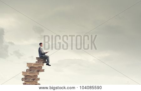 Young businessman sitting on pile of old book with one in hands