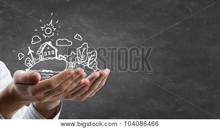 Person hands holding chalk drawn eco life concept