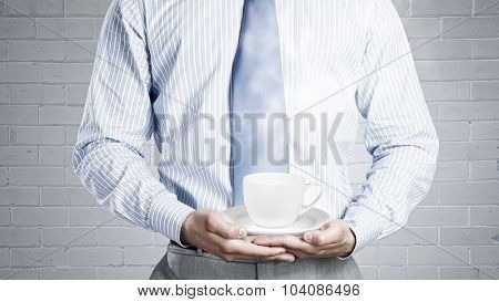 Close up of businessman holding in hands white cup