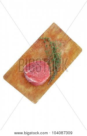 fresh red meat : raw beef fillet on wooden board with thyme ready to prepare . isolated over white background