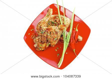grilled meat : chicken quarters garnished with green sprouts and red peppers on red plate isolated over white background