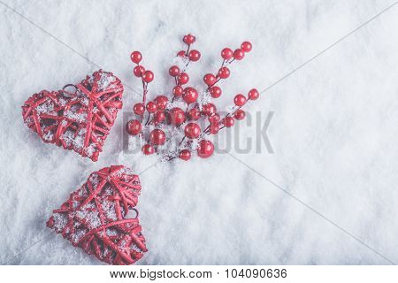 Two beautiful romantic vintage red hearts with mistletoe berries on a white snow winter background. Christmas, love and St. Valentines Day cozy concept.
