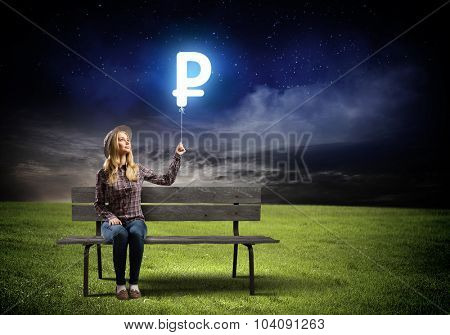 Young woman sitting on bench holding glowing balloon with ruble sign