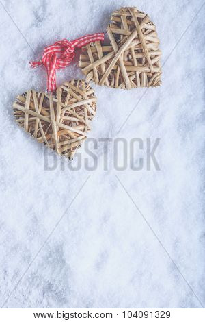 Two beautiful romantic vintage entwined beige flaxen hearts tied together with a ribbon on a white snow winter background. Love and St. Valentines Day concept.