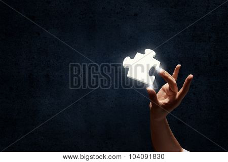 Person hand taking puzzle element with fingers