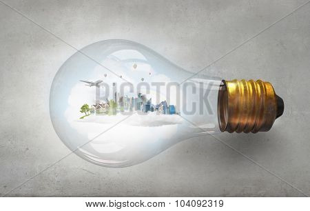 Glass light bulb with green life concept inside