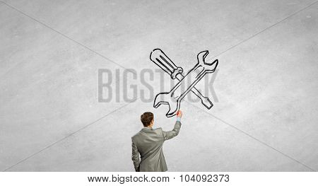 Rear view of businessman drawing tools on wall