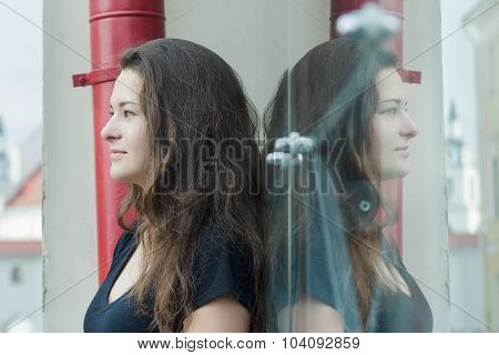 Glass Portrait Of Looking Forward Feminine Brunette Girl Posing Near Display Window With Symmetry Gl