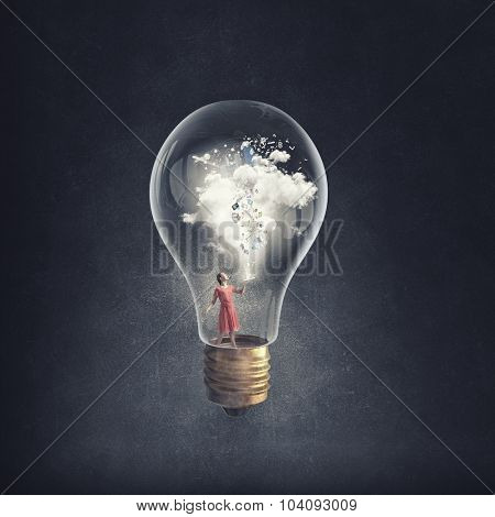 Young woman in dress with book in hands inside glass light bulb