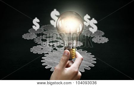 Gears mechanism and male hand holding glowing light bulb