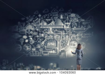 Back view of businesswoman drawing business strategy sketch on wall