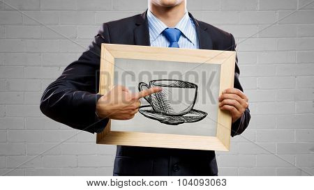 Businessman holding blackboard with drawn cup of coffee
