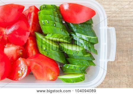 Slice cucumber and slice tomato in plastic lunch box