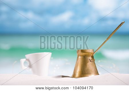 coffee pot and cup on beach with ocean, sky  and seascape. Shallow dof.