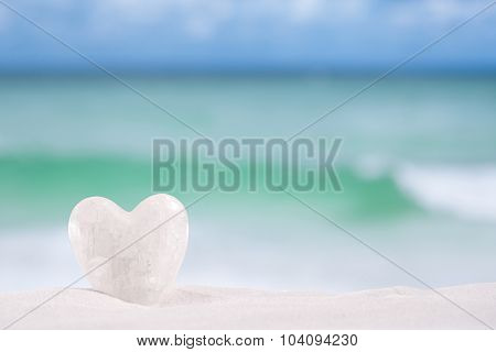 white crystal heart on white sand beach, ocean,  sky and seascape