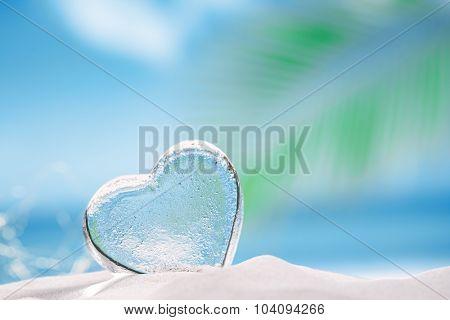 clear glass heart on white sand beach, ocean,  sky and seascape