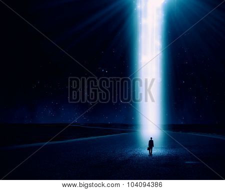 Rear view of businessman standing in light going from above