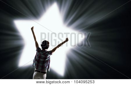 Rear view of woman with hands up in light of love