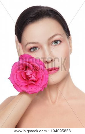 Portrait of young beautiful healthy mature woman with fancy pink rose over white background