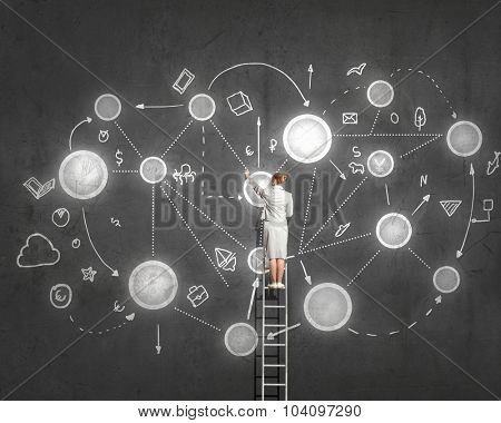 Rear view of woman standing on ladder and drawing life concepts on wall