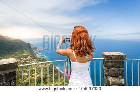 Woman takes photo of seaside landscape