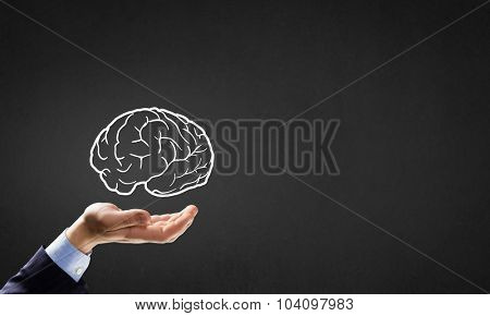 Person hand holding human brain in palm