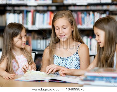 Little girls reading books in library