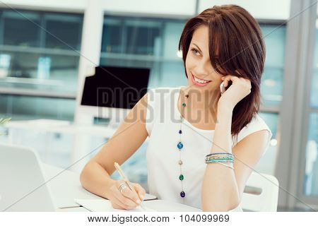 Modern business woman in the office with mobile phone
