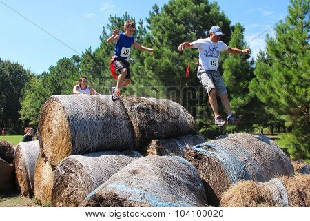 MUSKOGEE, OK - Sept. 12: Athletes jump over bails of hay to avoid bloody zombies during the Castle Zombie Run at the Castle of Muskogee in Muskogee, OK on September 12, 2015