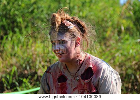 MUSKOGEE, OK - Sept. 12: An actor dressed as a zombie looks toward athletes during the Castle Zombie Run at the Castle of Muskogee in Muskogee, OK on September 12, 2015.