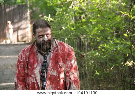 MUSKOGEE, OK - Sept. 12: A man in a bloody jacket waits to scare athletes during the Castle Zombie Run at the Castle of Muskogee in Muskogee, OK on September 12, 2015.