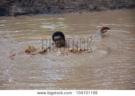 MUSKOGEE, OK - Sept. 12: A man acting as a zombie plays in the dirty pond, while waiting for runners during the Castle Zombie Run at the Castle of Muskogee in Muskogee, OK on September 12, 2015.