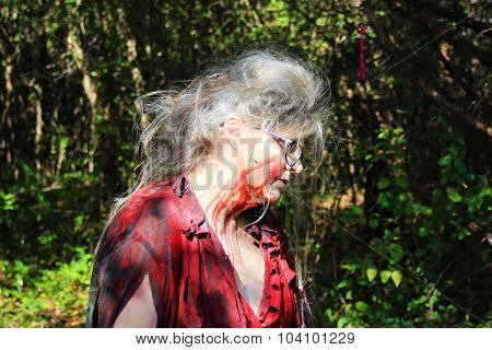 MUSKOGEE, OK - Sept. 12: An old woman with bloody face waits to scare athletes who try to avoid zombies during the Castle Zombie Run at the Castle of Muskogee in Muskogee, OK on September 12, 2015.
