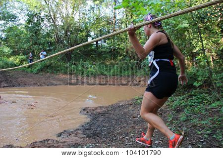 MUSKOGEE, OK - Sept. 12: A young athlete tries to avoid bloody zombies by crossing through a muddy pond during the Castle Zombie Run at the Castle of Muskogee in Muskogee, OK on September 12, 2015.